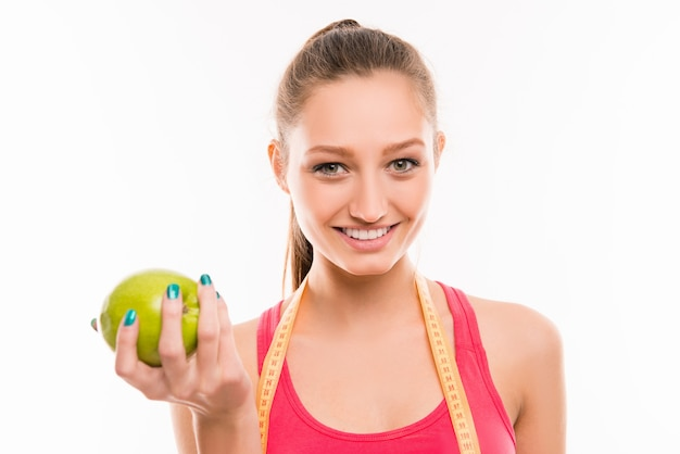 Pretty sporty girl with green apple in her hand