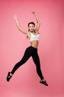 Pretty sporty woman in top and leggins jumping as ballerina