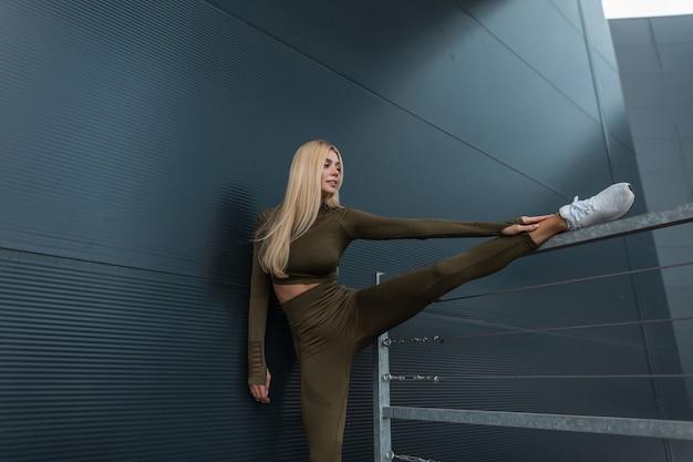 金属のモダンな壁の近くでトレーニングをし、足を伸ばす白いスニーカーとファッショングリーンのスポーツウェアのかなりスポーティーな若い女の子
