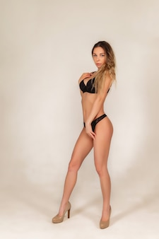 Pretty sporty young woman blonde with big breasts wearing black underwear posing on white background. naked female with healthy smooth skin shows emotion. concept of sexuality and beauty. copy space