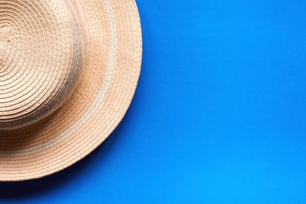 屋外用のかわいい麦わら帽子。青い背景、ビーチ帽子、上面図