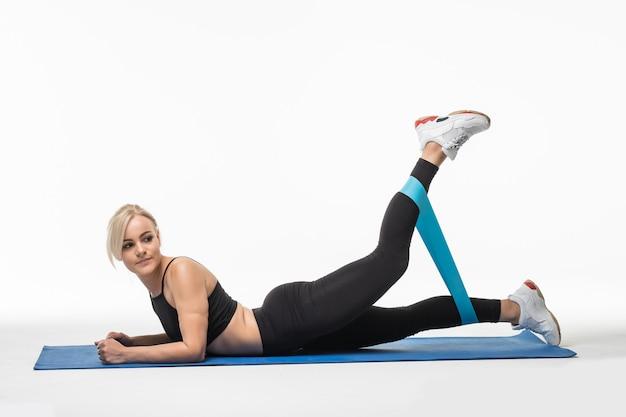 Donna abbastanza forte che fa esercizi di stretching sul pavimento in studio su bianco