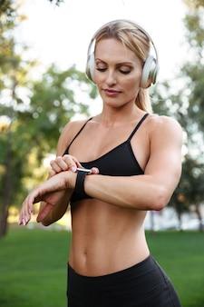 Довольно сильная молодая спортивная женщина слушает музыку и использует часы