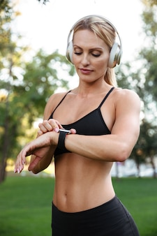 Pretty strong young sports woman listening music and using watch