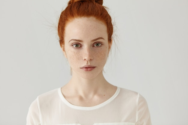 Pretty student girl with ginger hair in knot relaxing at home after college. headshot of tender charming young woman with freckles wearing white blouse posing
