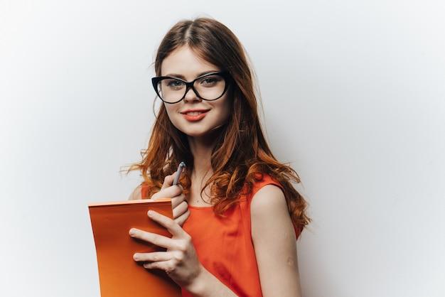 ライトの上で彼女の手で身振りで示すノートを持ったオレンジ色のサンドレスのかわいい学生