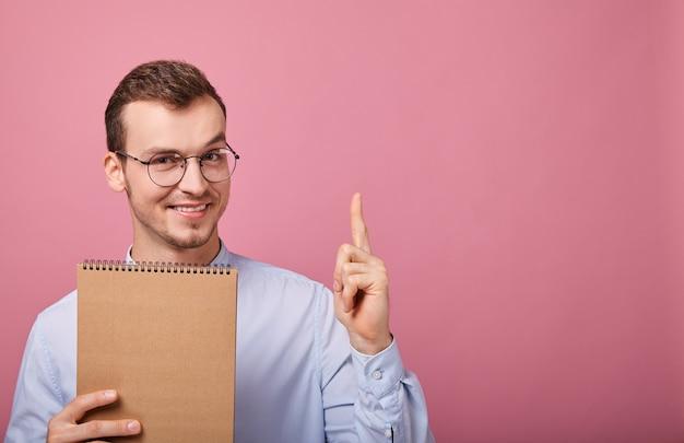 Симпатичная студентка в нежно-синей рубашке держит коричневую тетрадь и показывает
