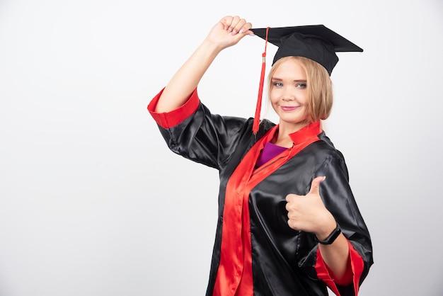 白い背景に親指を立てるガウンのかわいい学生。高品質の写真