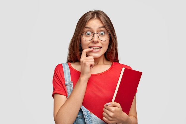 Симпатичная студентка смотрит с любопытным выражением лица, глаза полны интереса, удивления, кусает указательный палец
