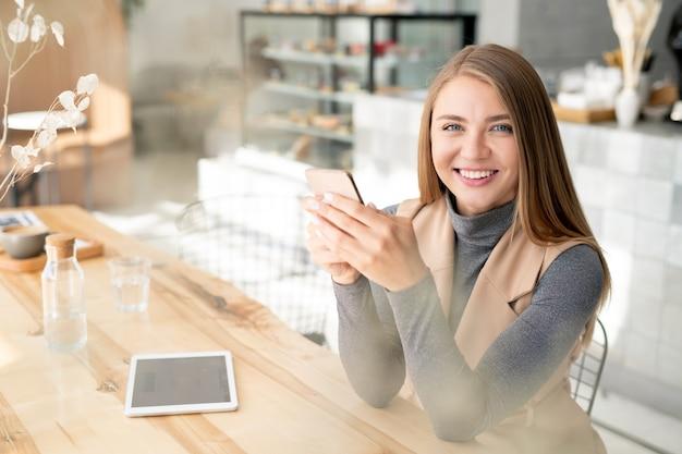 Симпатичная студентка или бизнес-леди в элегантной повседневной одежде с зубастой улыбкой во время использования мобильных гаджетов