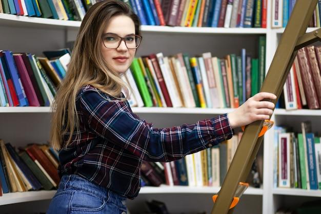 かなりの学生が図書館の脚立に立って、正しい本を見つけます。