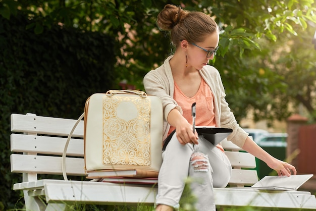 Симпатичная студентка учится на белой скамейке в парке.