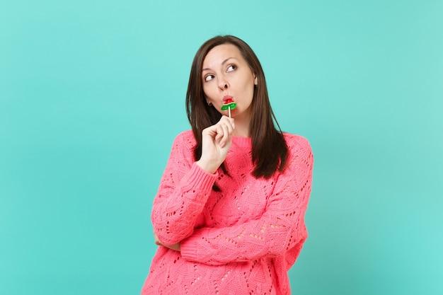 青い壁の背景、スタジオの肖像画に分離されたスイカのロリポップを手で舐めている見上げるニットピンクのセーターのかなり見事な若い女性。人々のライフスタイルの概念。コピースペースをモックアップします。