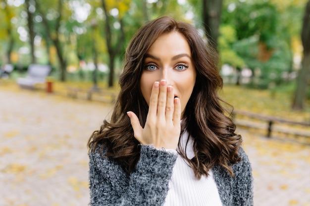 예쁜 스타일의 여자는 진짜 좋은 감정으로 공원에서 카메라에 포즈를 취하고 있습니다. 그녀는 놀란 표정으로 손으로 얼굴을 가리고 진정한 감정을 보여줍니다.