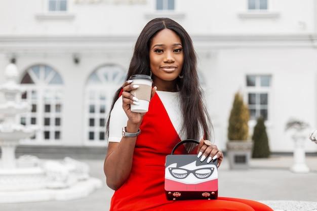 カップコーヒーとヴィンテージのハンドバッグとファッショナブルな赤い服を着たかなりスタイリッシュな黒人の若い女性は、通りの白い建物の近くのベンチで休んでいます。魅力的なアフリカの女の子はリラクゼーションと温かい飲み物を楽しんでいます