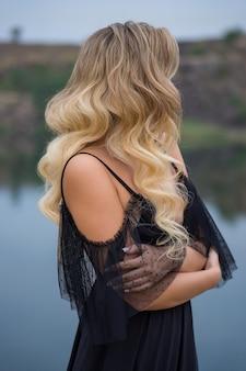 긴 곱슬 머리를 가진 꽤 세련된 금발 소녀, 세련된 아름다운 검은 드레스를 입고 자연 배경에 포즈.