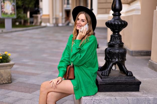 Довольно стильная блондинка позирует в европейском старом городе, держа в руке телефон