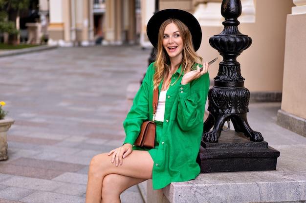 Donna bionda abbastanza elegante in posa nella città vecchia europea, tenendo in mano il suo telefono