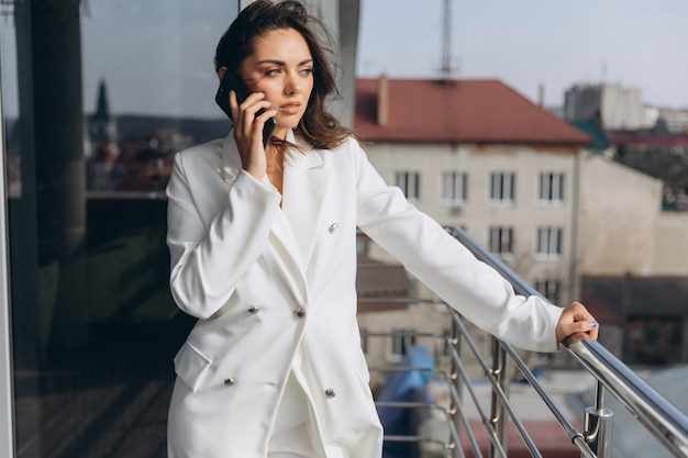 Pretty stylish business woman stands on the balcony near modern office and talking on the smartphone.