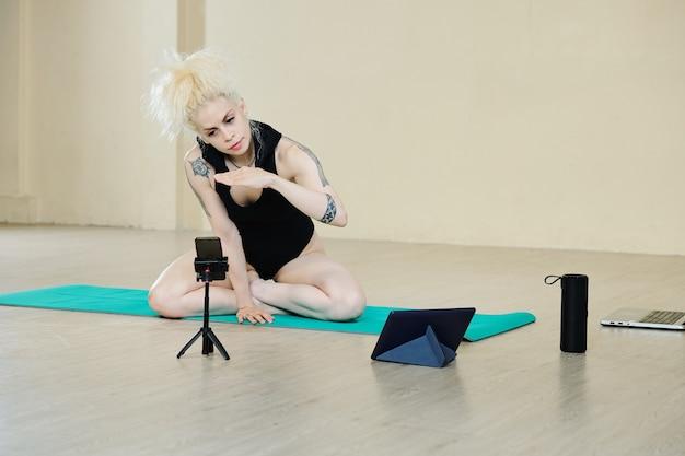 Довольно стильная танцовщица сидит на коврике для йоги и разговаривает со студентом во время онлайн-урока, который она проводит