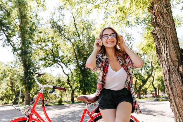 夏の公園で朝を楽しむかなりスタイリッシュな女性モデル。自転車でポーズをとって笑う楽しい女の子の屋外の肖像画。
