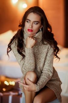 髪型と化粧がソファーに座っていたドレスでかなりスタイリッシュな女の子。ファッションの魅力の肖像画。
