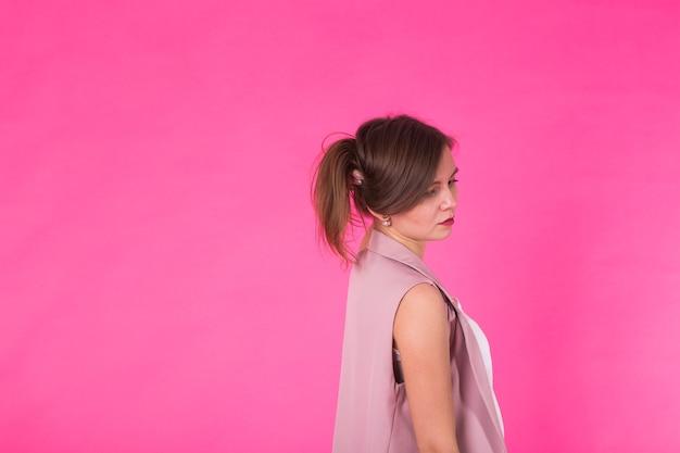 ピンクの背景にポーズをとる長い髪のかなりスタイリッシュな女の子。若い幸せな笑顔の女性のファッションの肖像画