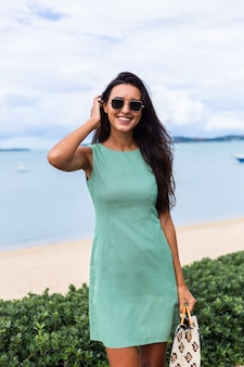 Pretty stylish happy woman in green summer dress with bag, wearing sunglasses on vacation, blue sea on background