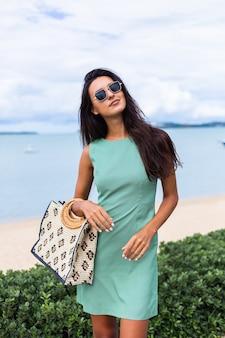 Довольно стильная счастливая женщина в зеленом летнем платье с сумкой, в темных очках на отдыхе, синее море на фоне