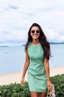 가방 녹색 여름 드레스에 꽤 세련 된 행복 한 여자, 휴가에 선글라스를 착용, 배경에 푸른 바다