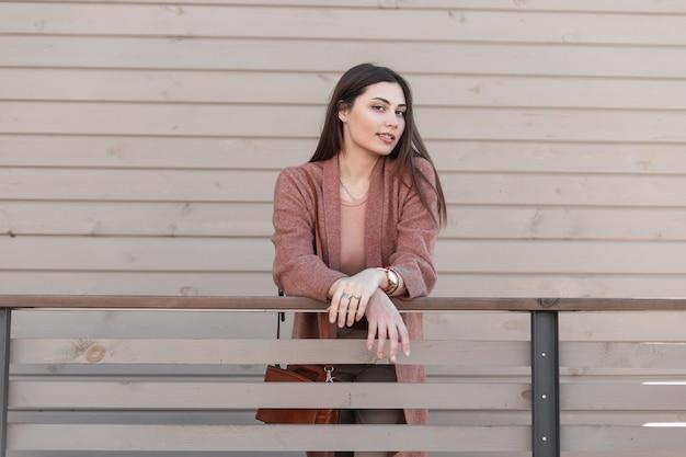 유행 봄 코트에 긴 머리를 가진 꽤 세련된 사랑스러운 젊은 여성 패션 모델은 거리에 나무 난간 근처에 서있다. 트렌디 한 캐주얼 겉옷에 아름다운 귀여운 소녀는 도시에서 휴식을 즐깁니다.