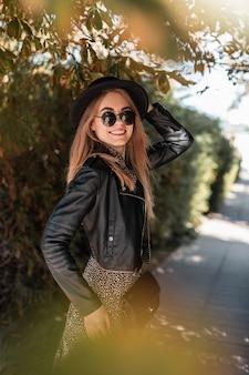 Довольно стильная улыбающаяся женщина в модном наряде выглядит с кожаной курткой и винтажным платьем на прогулке на открытом воздухе
