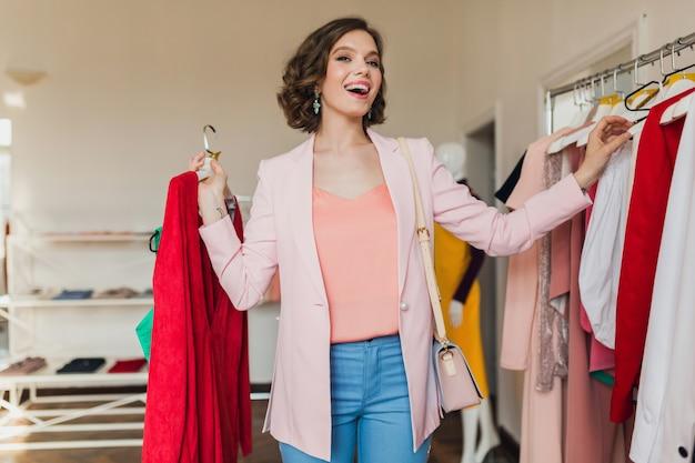 Donna abbastanza elegante scegliendo abbigliamento in negozio