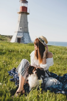 Pretty stylish woman in countryside, holding a dog, happy positive mood, summer, straw hat, bohemian style outfit