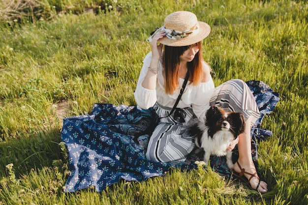 Pretty stylish woman in countryside, holding a dog