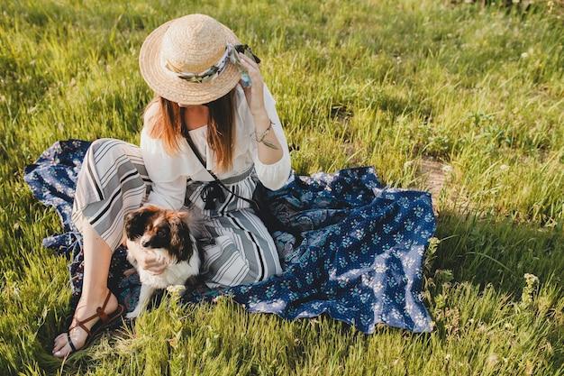 Довольно стильная женщина в сельской местности, держа собаку, счастливое позитивное настроение, лето, соломенную шляпу, наряд в богемном стиле