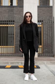 通りのモダンな建物の近くにファッショナブルなtシャツと白い靴のヴィンテージデニムパンツのファッションロングジャケットのかなりスタイリッシュな女性。トレンディな春の装い。カジュアルファッション。ブラックスタイル。