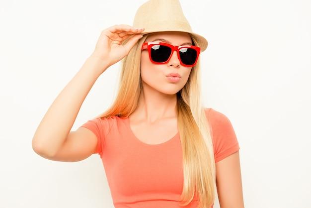 Довольно стильная женщина в очках, касаясь ее шляпы и надувшись