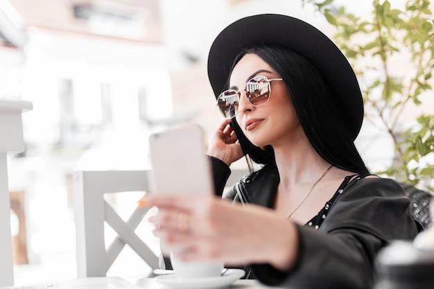 おしゃれな服を着たヴィンテージサングラスの流行の帽子をかぶったかなりスタイリッシュな女性がカフェに座って、スマートフォンで自分撮りをします。黒人の若者が着ている魅力的な女の子は、コーヒーを飲み、自分の写真を撮ります。