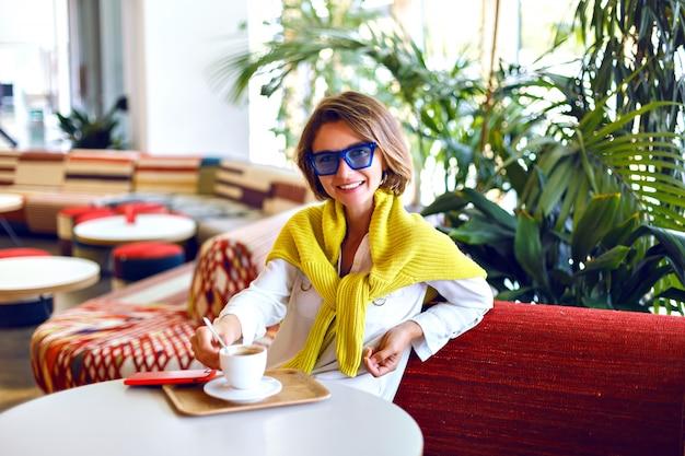 Довольно стильная женщина позирует в ресторане, пальмы вокруг, в солнцезащитных очках и желтом неоновом свитере, повседневный элегантный вид, естественный макияж, короткая прическа.