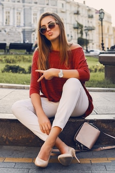 Pretty stylish woman in trendy sunglasses and red sweater sitting on the street