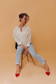 Donna abbastanza elegante con i capelli raccolti e le labbra rosse che si siedono sopra la parete beige isolata
