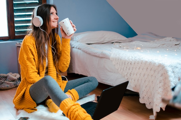 커피를 마시고 그녀의 침실에서 노트북을 사용하는 헤드폰으로 꽤 세련된 여자. 온라인 공부 휴식에 화상 채팅을하는 바닥에 아늑한 앉아. 복사 공간