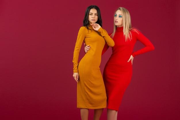 Довольно стильные женщины в желтых и красных осенне-зимних модных вязаных платьях позируют изолированно на красной стене