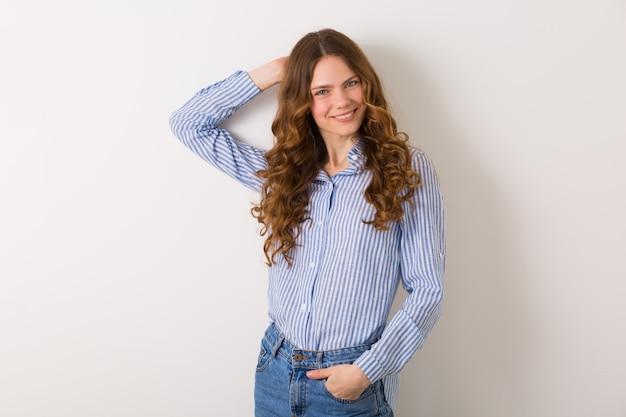 Giovane donna abbastanza alla moda che posa in attrezzatura di stile del denim su bianco