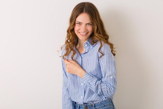 Довольно стильная молодая женщина позирует в джинсовой одежде на белом