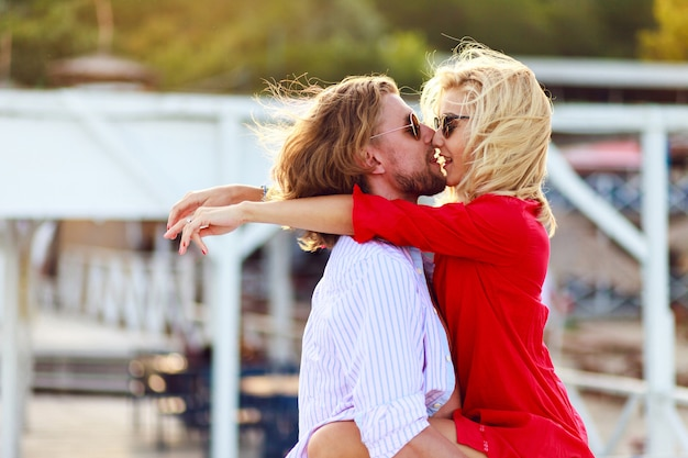 Pretty summer sunny outdoor portrait of young stylish couple while kissing and hugging on the street