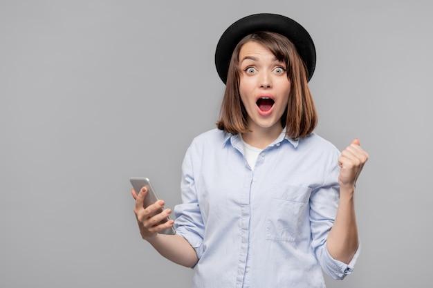 Довольно удивленная девушка в шляпе и рубашке смотрит на вас, держа смартфон с промо распродажи