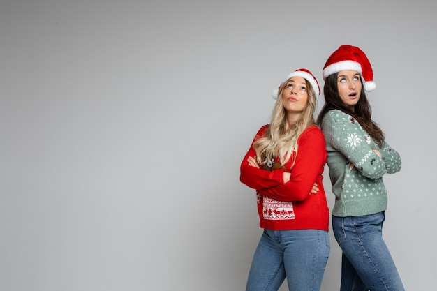 コピースペースで灰色のスタジオの背景にポーズをとってサンタの帽子と冬のセーターでかなり驚いた若いクリスマスの女の子