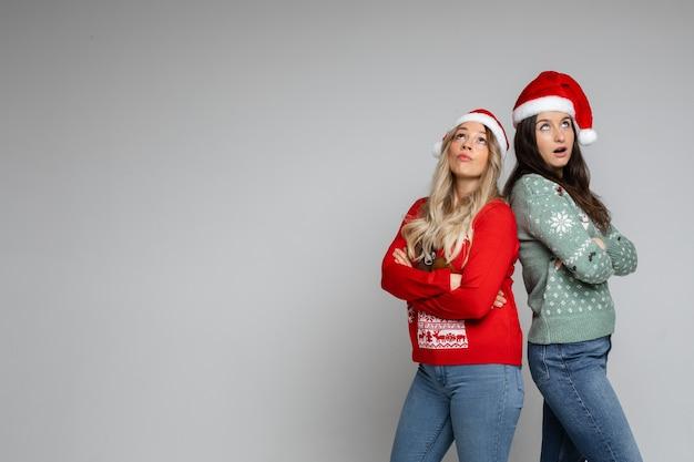 Giovani ragazze di natale abbastanza sorprese in cappelli di babbo natale e maglioni invernali in posa su sfondo grigio studio con spazio copia